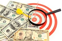 Money dollars and magnifying glass on darts target