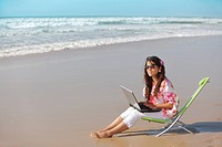 young woman relaxing and using laptop on wild beach