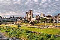 Cityscape of buildings and park near river in town.