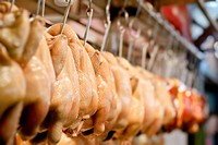 Chicken, lot of raw meat hanging in marketplace.