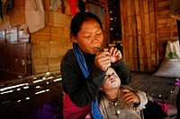 A Burmese mother lights her pipe in her hut while her baby watches In Myanmar Burma, thousands of people have settled near the border as a result of o...
