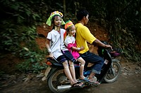 Members of a Longneck family ride on a moped Approximately 300 Burmese refugees in Thailand are members of the indigenous group known as the Longnecks...