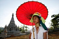 A young Longneck girl poses in front of a temple holding a bright red parasol Approximately 300 Burmese refugees in Thailand are members of the indige...
