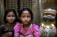 Two children are sitting near a temple in Katmandu The statue is a lion