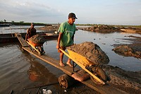 Poor people dig sand from the bottom of the river and transport it with canoes to the shoreline and sell it to businessmen