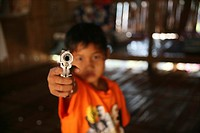 A young refugee aims a handgun at the camera Around 130,000 Burmese refugees have settled in Thailand due to opression in their homeland of Myanmar Bu...