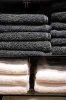 Gray and White Towels Stacked on Shelves in a Retail Store Display