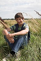 teenage boy sitting on grass bank in countryside