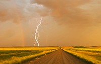 electrical storm over gravel road between farmland, near Val Marie, Saskatchewan