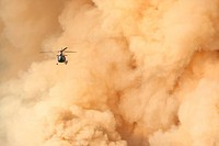 Helicopter flying in to fight a forest fire burning off the David Thompson Highway in Alberta, Canada