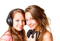 Teen radio, two gorgeous cute brunette teen girls having fun with headphones and music.
