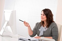 Young business woman working with computer at office sitting at desk