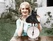 Portrait of a young woman weighing her puppy on a weighing scale All persons depicted are not longer living and no estate exists. Supplier warranties ...