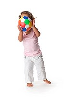 Toddler girl hiding behind a colored ball on white background