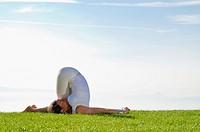 Young woman practising Hatha yoga outdoors, showing the pose variation of halasana, karnapidasana, variation of plough, Nove Mesto, Okres Teplice, Cze...