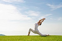 Young woman practising Hatha yoga outdoors, showing the pose anjaneyasana, chandrasana, half moon pose, Nove Mesto, Okres Teplice, Czech Republic, Eur...