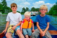 Three blond boys in a boat on the water