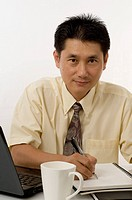 Asian businessman sitting at desk writing report