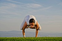 Young woman practising Hatha yoga outdoors, showing the pose kakasana, bakasana, crow pose, crane pose, Nove Mesto, Okres Teplice, Czech Republic, Eur...
