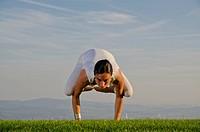 Young woman practising Hatha yoga outdoors, showing the pose kakasana, bakasana, crow pose, crane pose, Nove Mesto, Okres Teplice, Czech Republic, Eur...