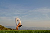 Young woman practising Hatha yoga outdoors, showing the pose surya namaskar 5, sun salutation 5, Nove Mesto, Okres Teplice, Czech Republik, Europe
