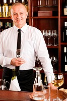 At the bar _ waiter hold bottle white wine in restaurant