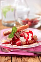 Pastry with cream, sweet sauce and cranberries