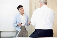 Businesswoman standing next to a white board during a presentation.
