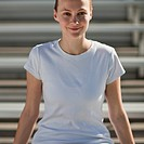 Beautiful young woman smiles while sitting on bleachers.