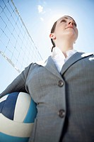 Businesswoman stands at a volleyball net and holds a volleyball in her hands.