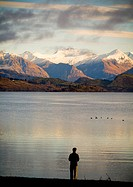 Man views mountains at sunrise with lake in foreground