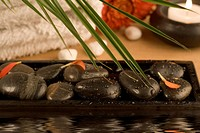 Spa setting with white towels, pebbles, candles and palm leaf reflected in water