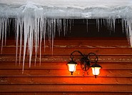 Icicles hanging from roof on idyllic wood cabin