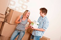 New house: Young couple with box in new home unpacking book, woman with mobile phone