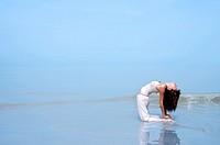 Woman practising YogaCamel Pose on the beach.