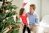 A father and his daughter wearing a moose antler sitting next to a Christmas tree