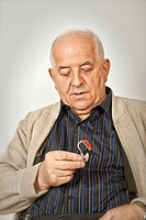 Senior holding a hearing aid device