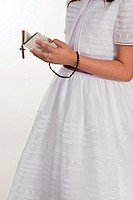 Girl dressed in First Communion with prayer book