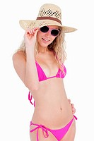 Young attractive blonde teenager in beachwear holding her hat brim