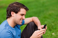 Young man sending a text with his mobile phone while sitting in a public garden