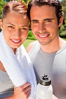 Smiling man holding a sports bottle with a woman who is smiling while holding a towel