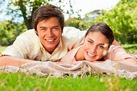 Man and a woman smiling and looking straight in front of them while lying prone on a grey blanket