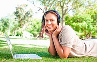 Young woman with a laptop and headphones lying on the lawn