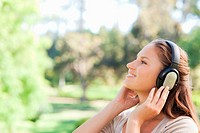 Side view of a young woman in the park enjoying music