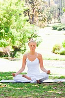 Young woman sitting in a yoga position on the grass