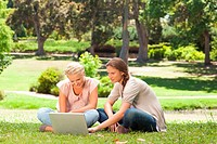 Female friends sitting on the lawn with a laptop