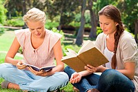 Female friends reading books in the park