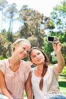 Young woman taking a picture of herself and a friend