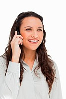 Pretty brunette smiling while phoning against white background