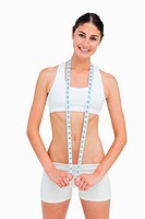 Slim woman with a measure tape against white background